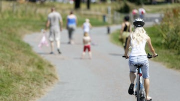 Lady cycles along Saltram estate pathway with families walking in the distance