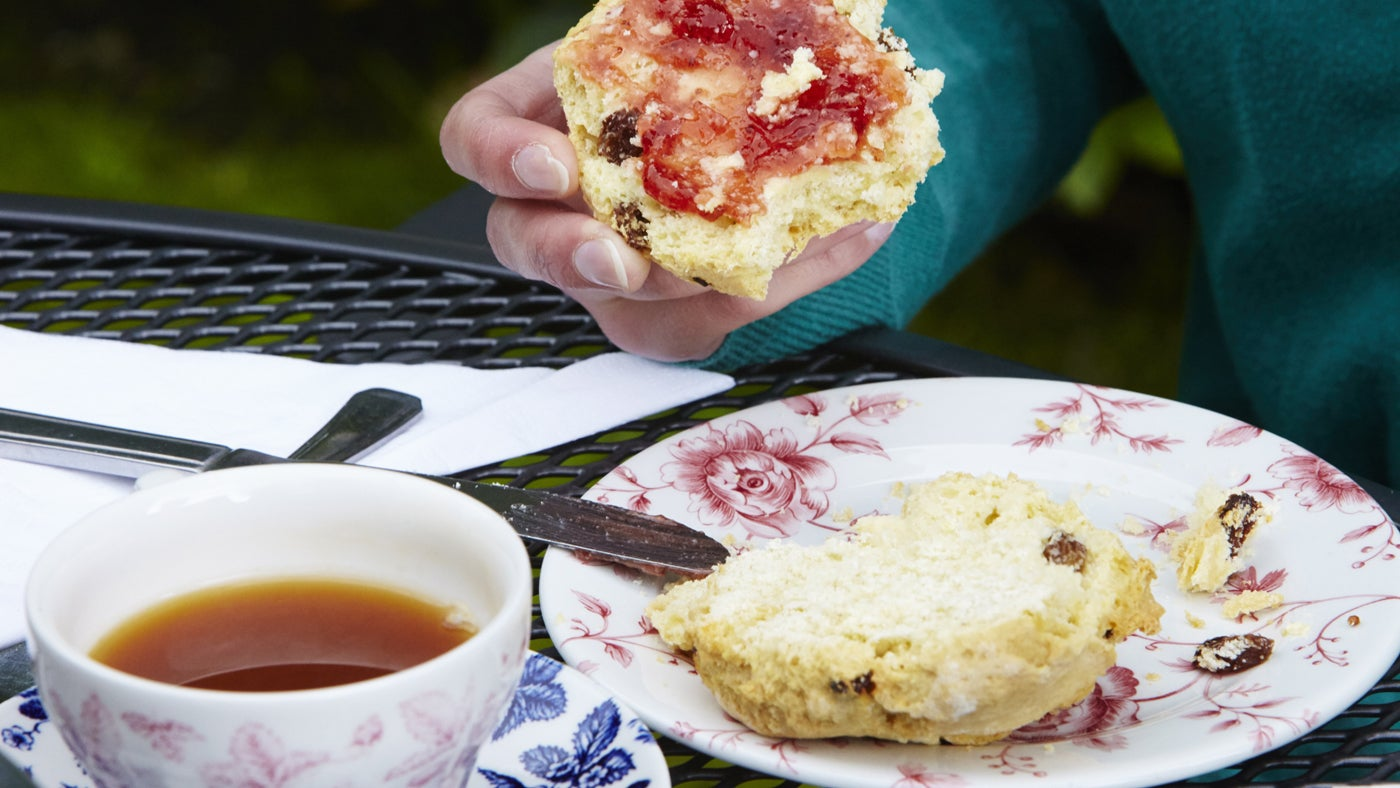A visitor enjoying a traditional scone with jam and cream at one of the National Trust tea-rooms