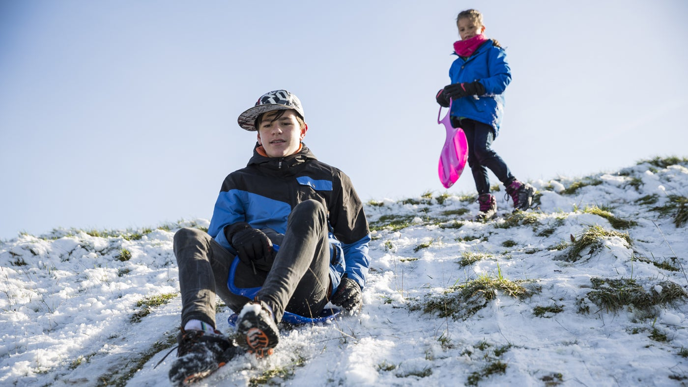 Children sledging down a snow-covered hill in the winter at a National Site