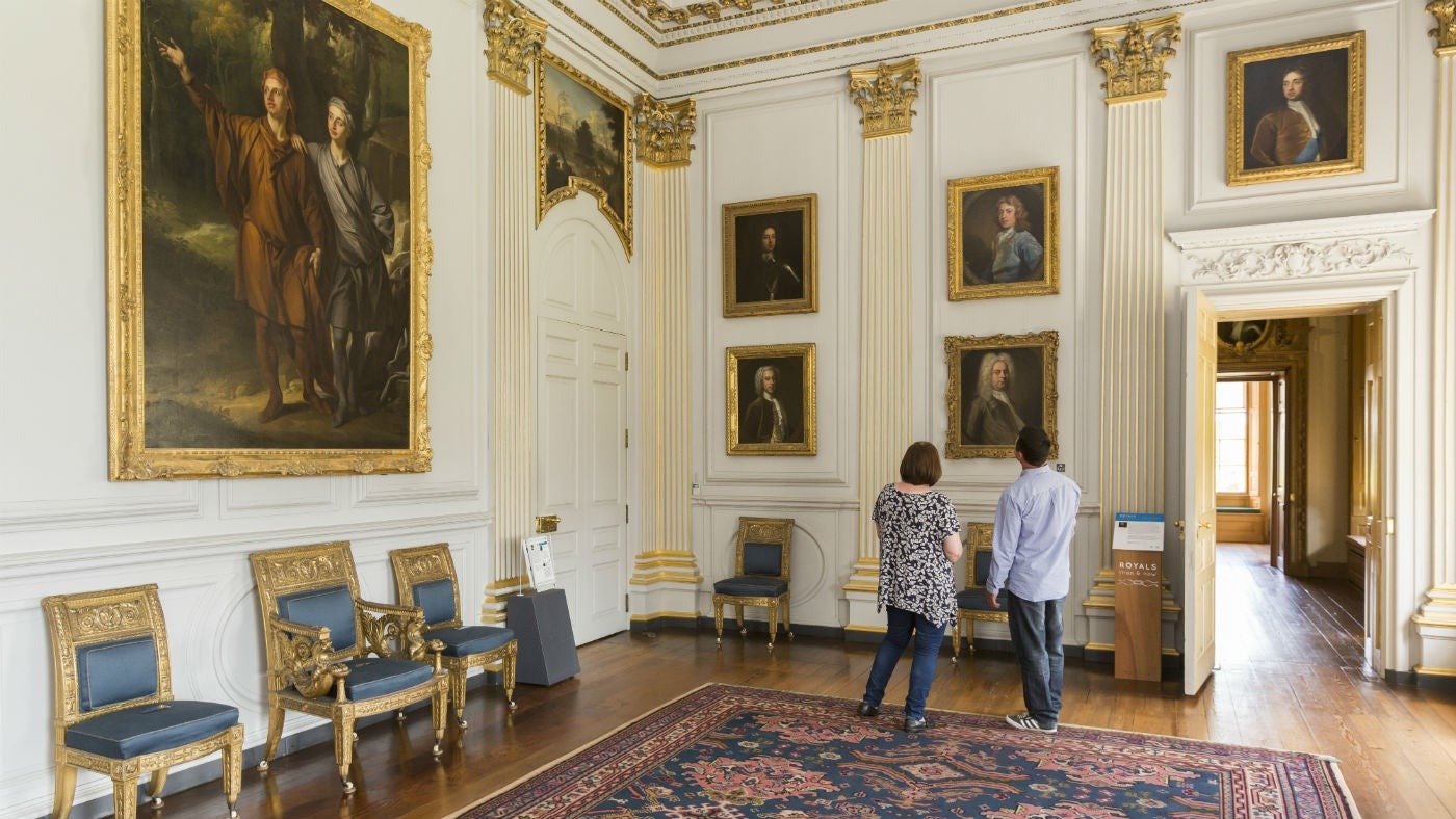Two people looking at art on the walls of a large baroque room