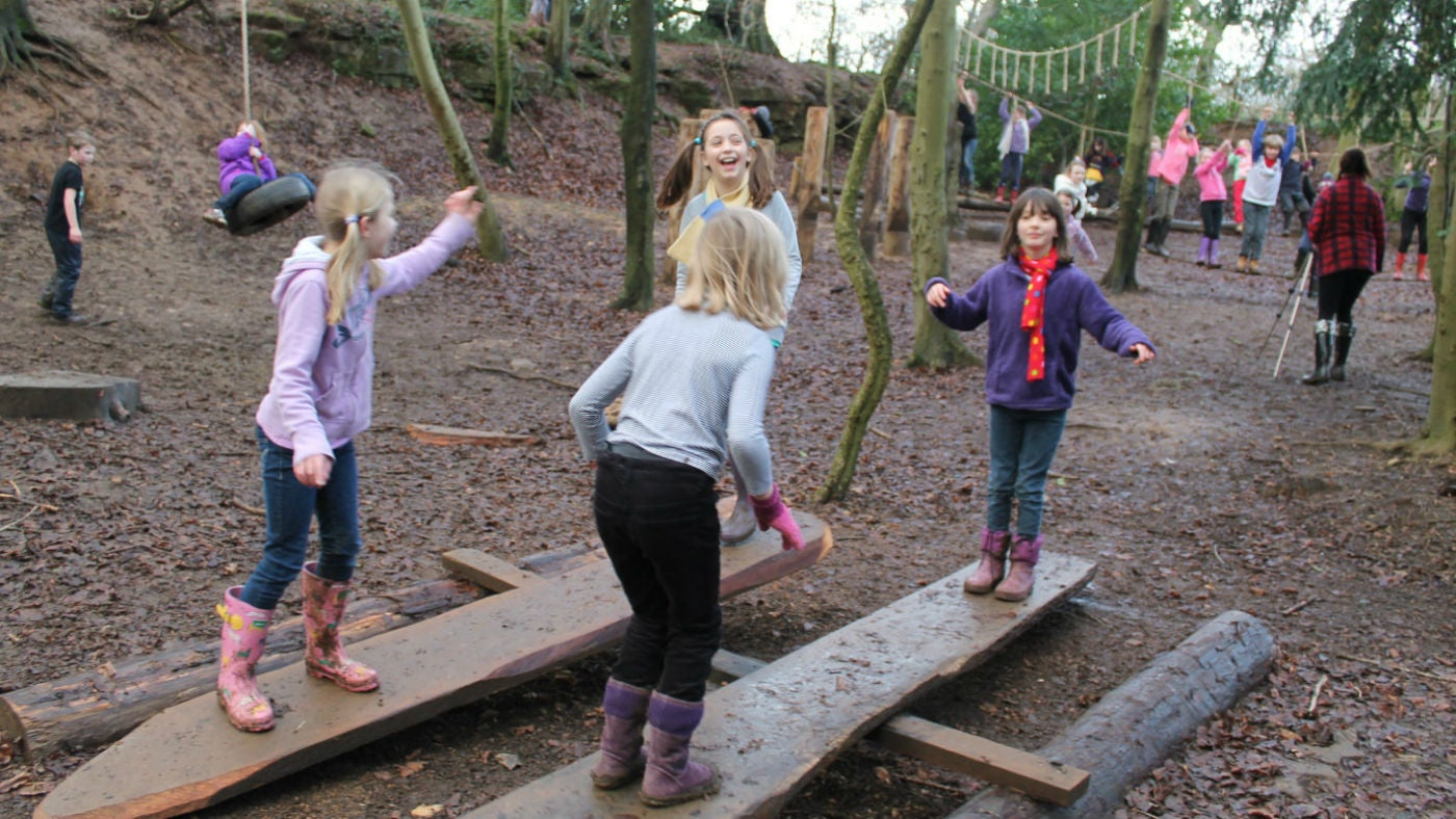 Children on the see-saw planks at the Woodland Play Area