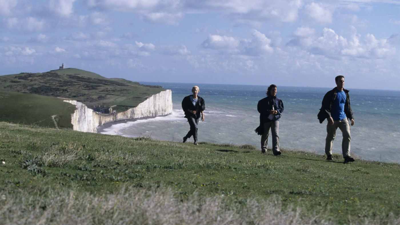 Three people walk along the top of the magnificent Seven Sisters cliffs with distant views behind of sea , horizon, Birling Gap coastguard cottages and Belle tout lighthouse