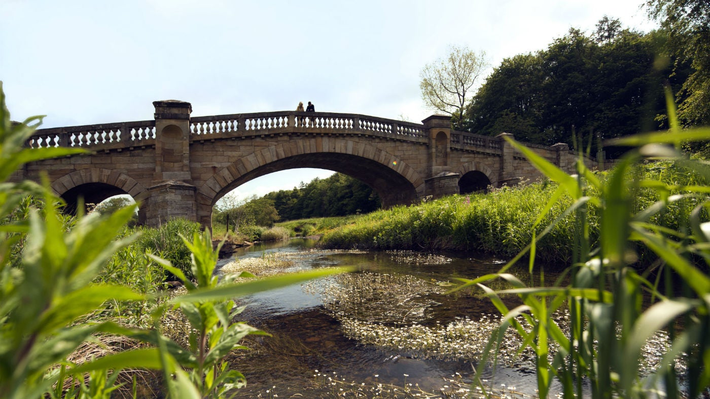 Two visitors walking over the bridge over the River Wansbeck, Northumberland