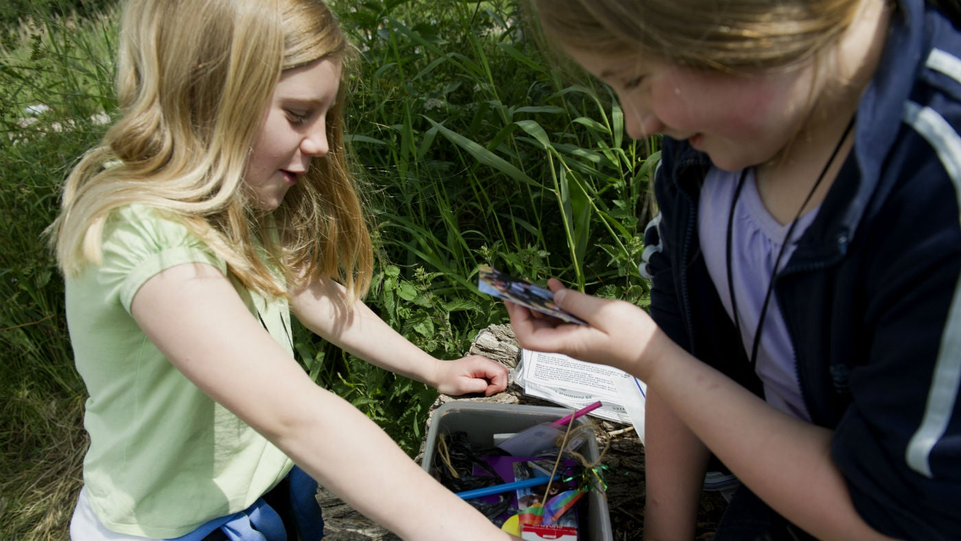 Two girls looking at a geocache at Roseberry Topping