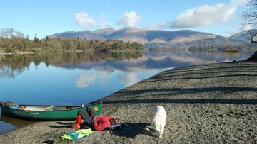 Canoe and dog on Derwentwater lakeshore, Cumbria