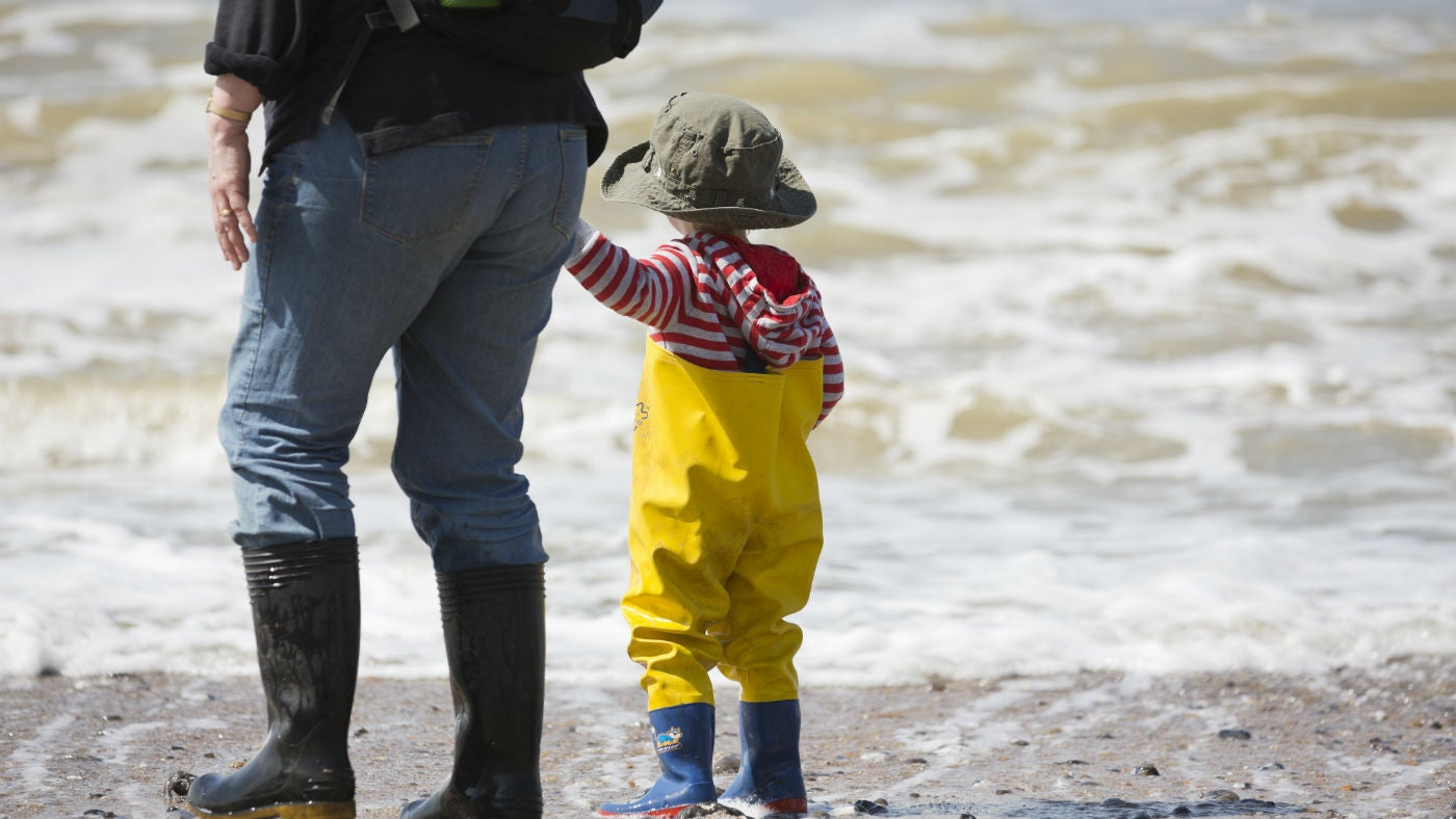 A woman and child wearing wellies paddle in the waves Durham Coast