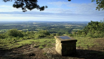 A view south looking over the rolling downland of the South Downs from behind the stone plinth, with a charming curved inscribed stone seat in memory of WE Hunter who donated Black Down to the National Trust in memory of his beloved wife.