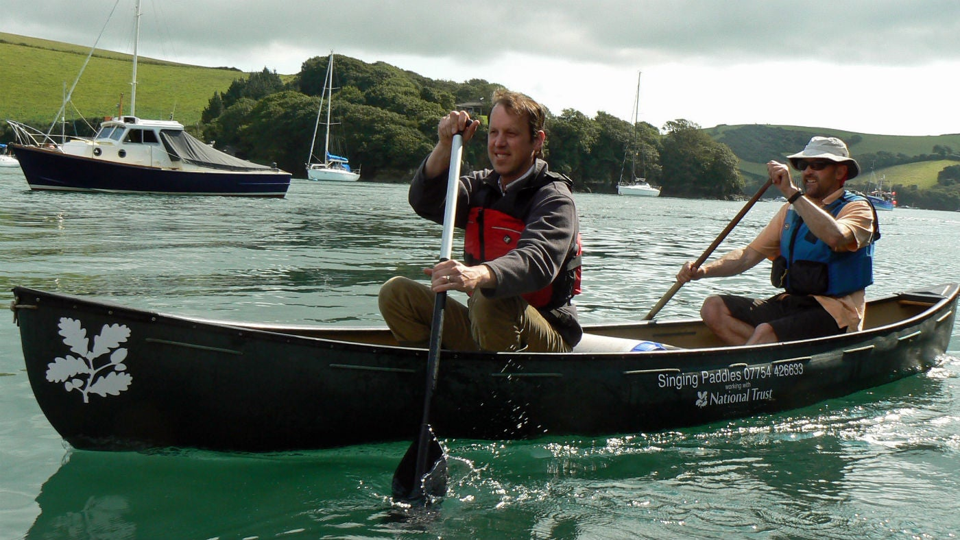 Two men paddle a National Trust canoe