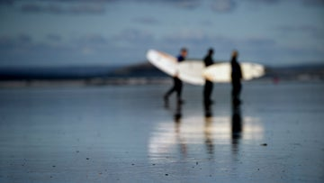 Surfers on the sand of Rhossili Bay, Gower, Swansea, Wales.