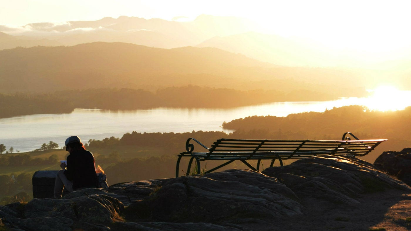 A woman sitting at Orrest Head during the sunset