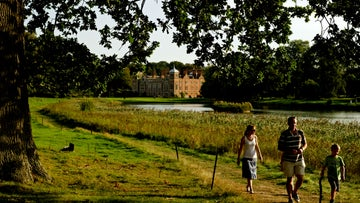 Family visitors walking around the lake at Blickling Estate, Norfolk