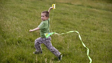 A small boy runs ascross the grass flying a kite at a National Trust site