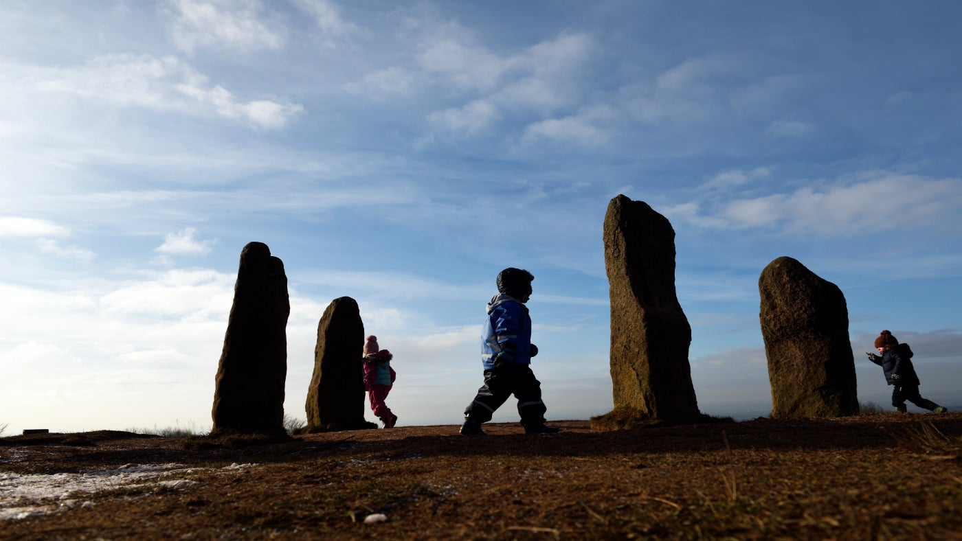 Children running around the four standing stones on top of Clent Hill