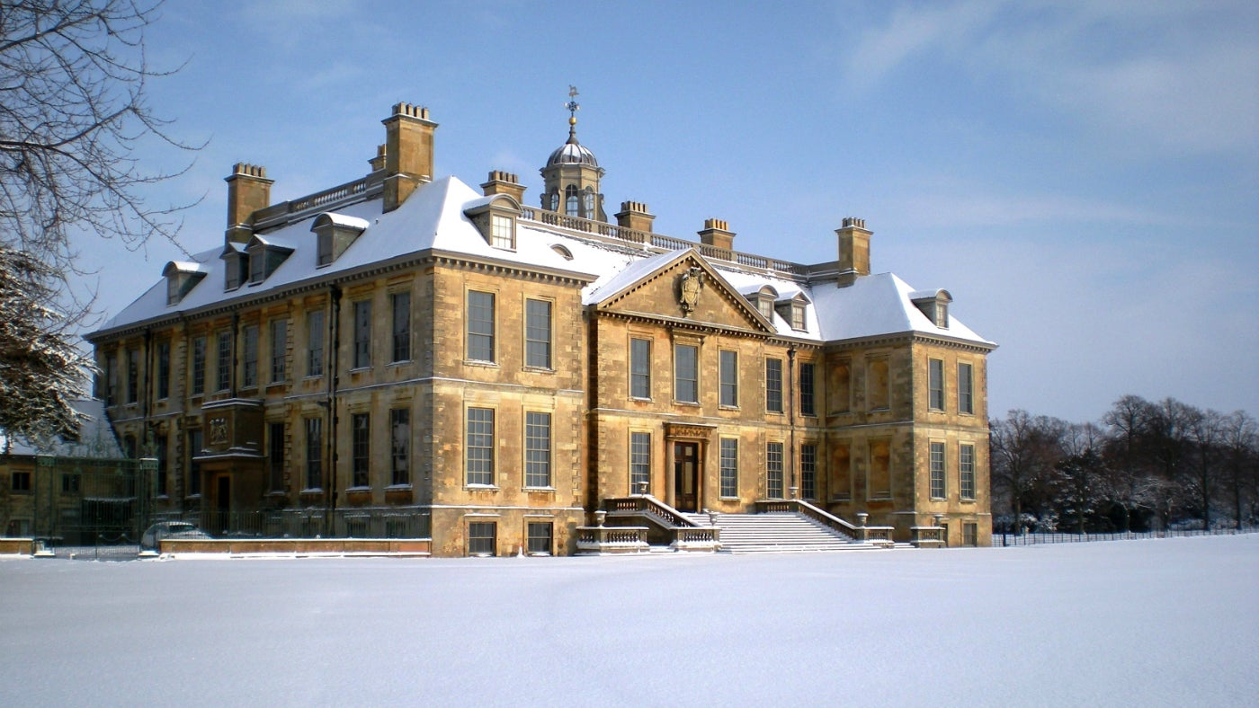 Belton House covered in snow on a clear winter's day
