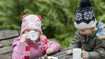 Little girls and boy wearing wooly hats, with hot chocolate and cake at Ickworth