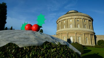 Garden hedge decorated as a Christmas pudding with the Rotunda in the background