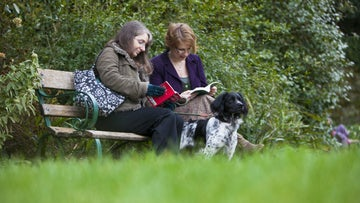 A dog with his owners in the garden of Greenway, Devon