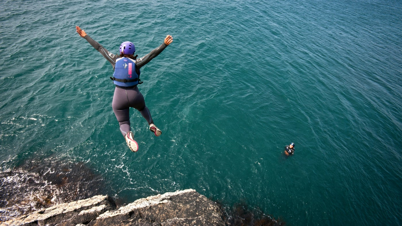 Lady jumping into the sea as part of coasteering group