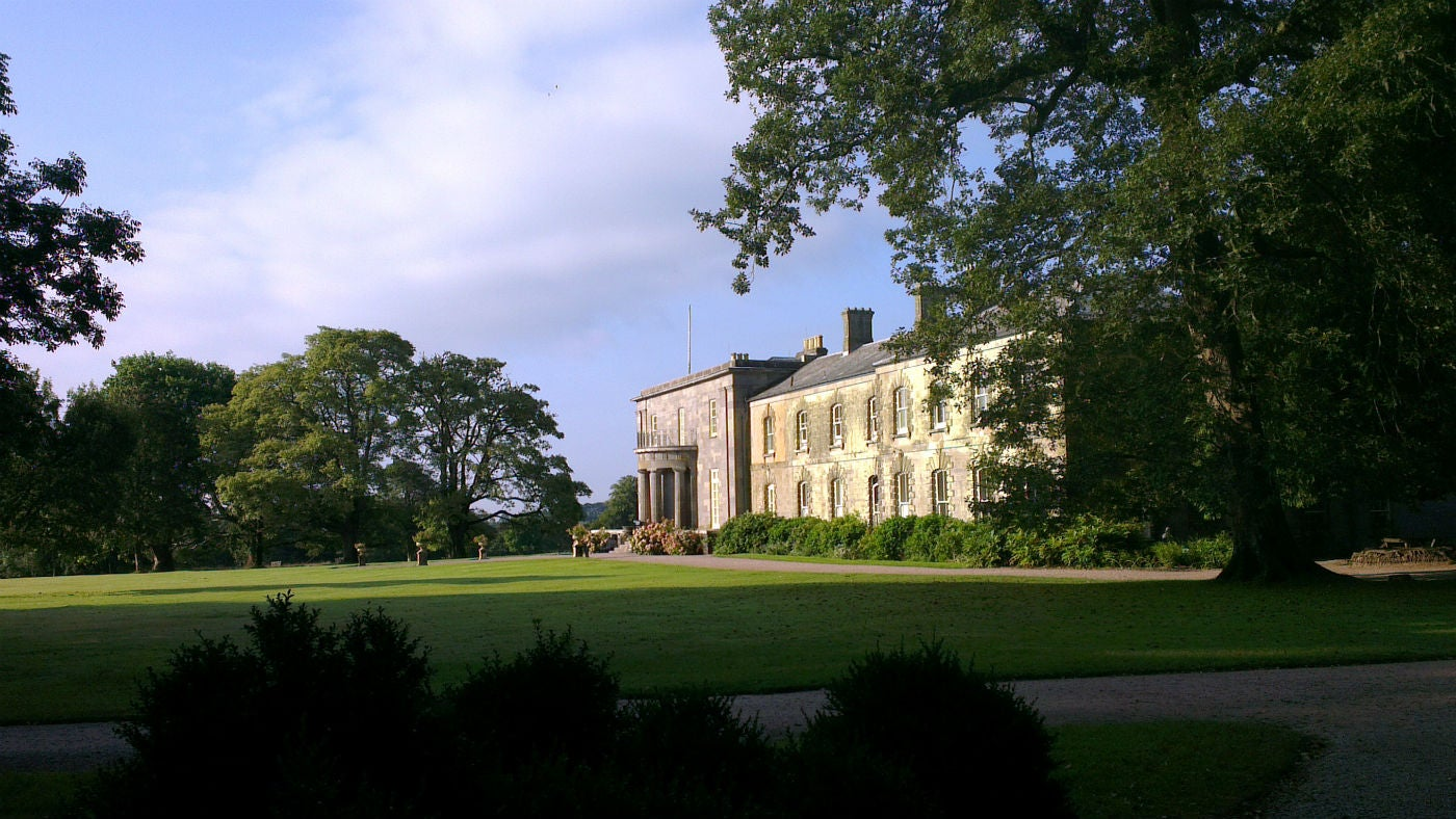 A view of Arlington Court across the lawn on a summer morning