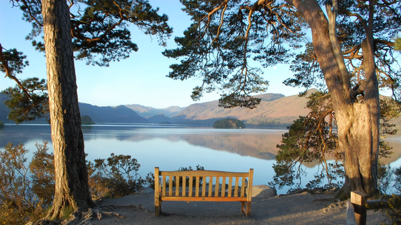 The bench at the viewpoint at Friar's Crag, Derwent Water with hills reflected in the lake