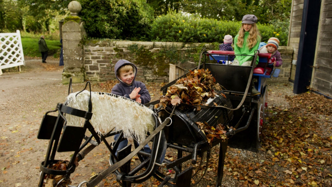 Children play on the play carriage in the stableyard at Arlington Court