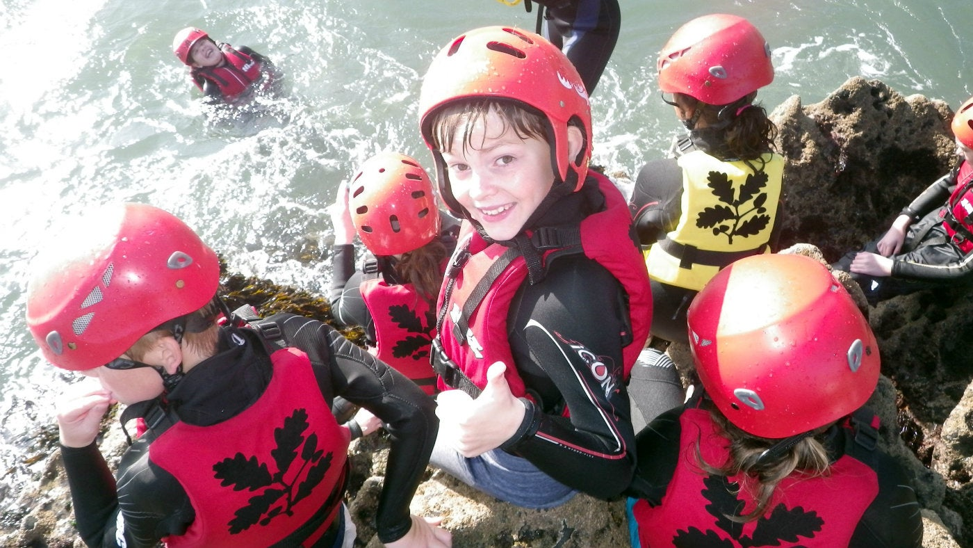 Children taking part in coasteering at Stackpole
