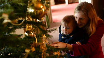 Little girl and mother admiring the Christmas tree