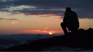 walker watching sunset on Mam Tor