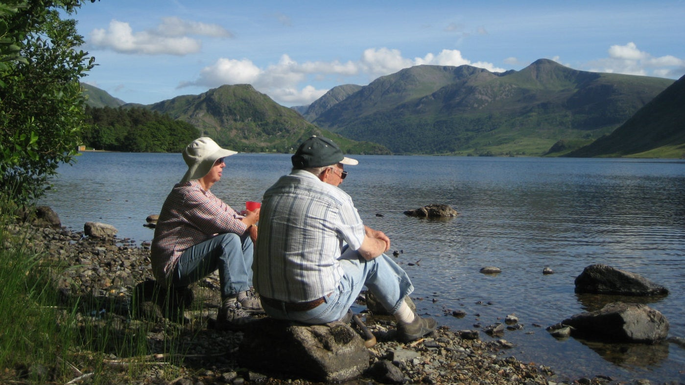 Couple rest beside Crummock Water, Cumbria