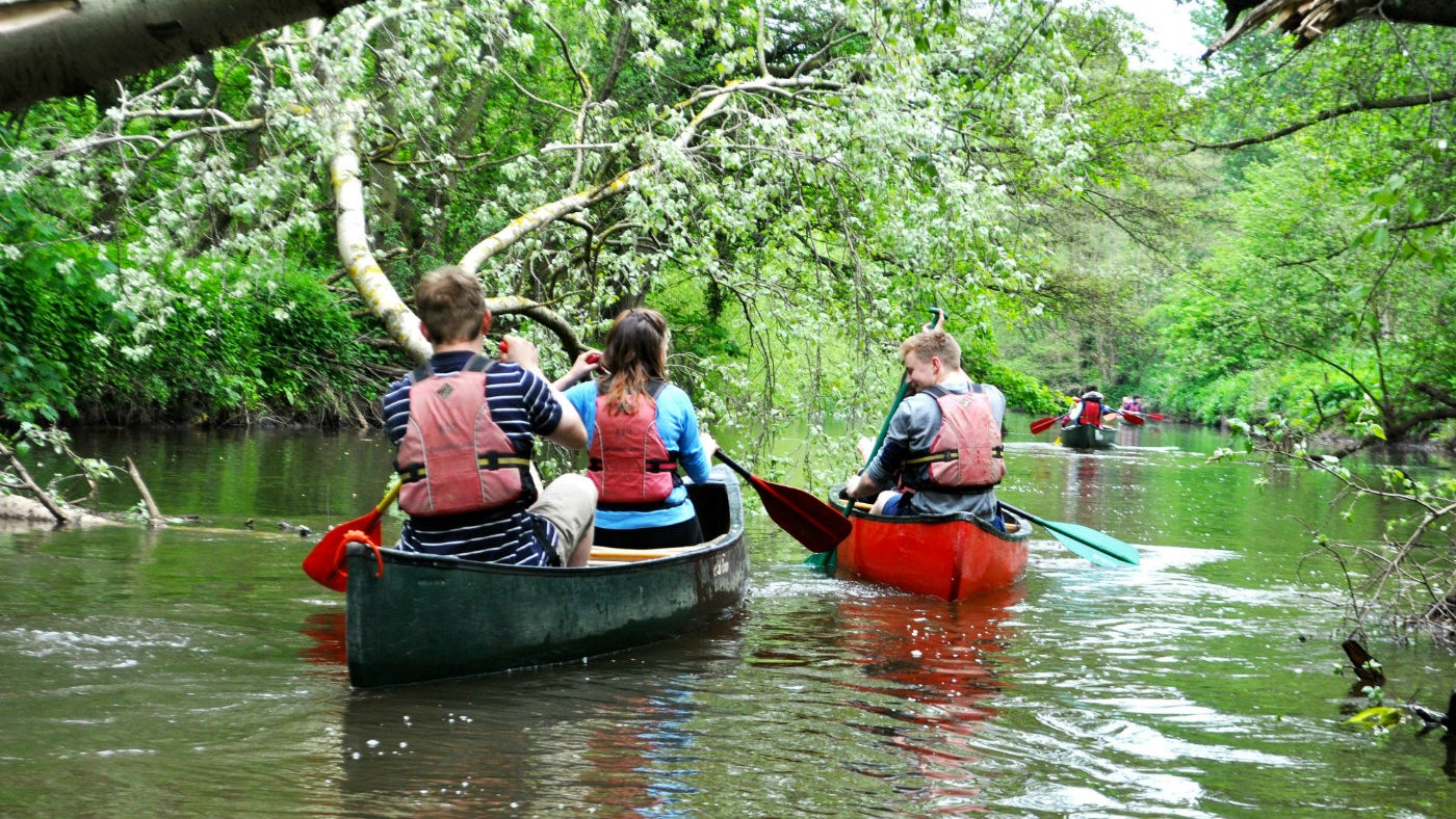 Four canoes sailing down the river Tern full of people having a great time