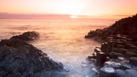 Picture shows the sun setting on the horizon at the Giant's Causeway