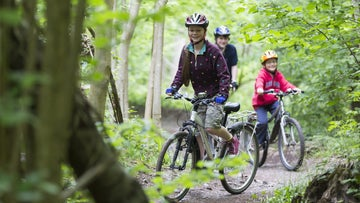 Family cycling through Leigh Woods, Bristol