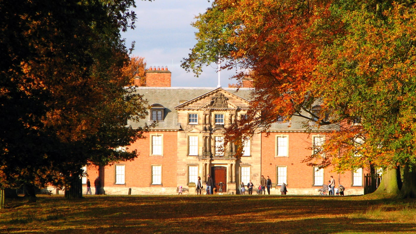 Dunham Massey Hall lined with autumn trees