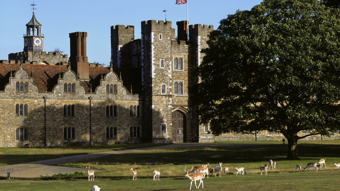 Deer wander through Knole Park outside the West Front entrance of Knole in Sevenoaks, Kent