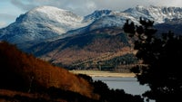 Snow-capped peaks of the Ennerdale skyline with a glimpse of Ennerdale Water through wintery trees