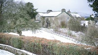 A view of Hill Top garden and house covered in snow, Cumbria
