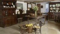 The Buttery with a wooden table and dresser, and the original rough limeash concrete floor at Bradley Manor, a medieval house at Newton Abbot, Devon