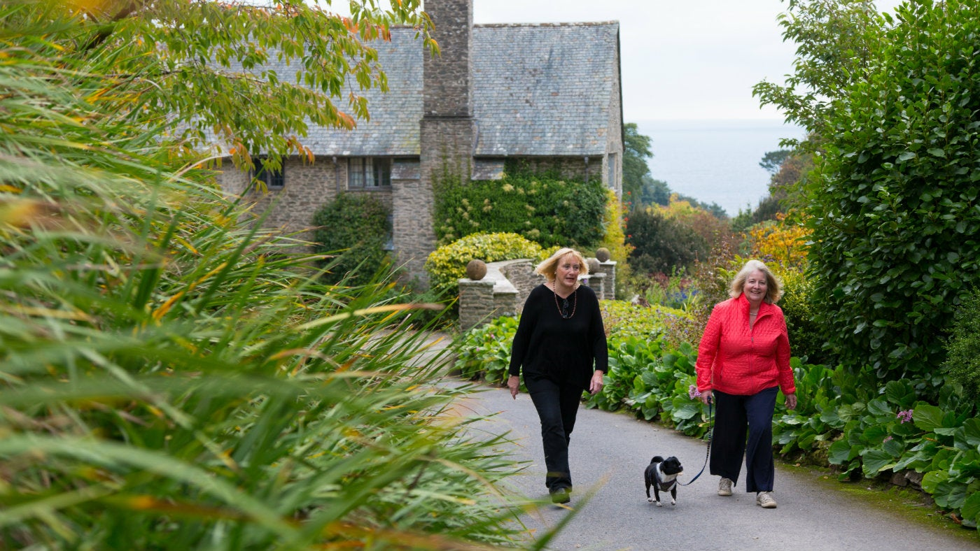 Two women walking their dog near Coleton Fishacre house