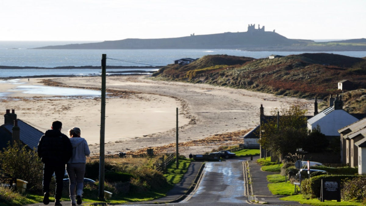 Visitors walking into Low Newton with Dunstanburgh Castle in the distance