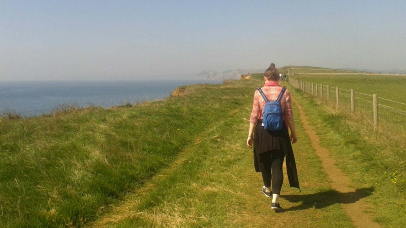 A female walker on the coast path near Burton Bradstock on a sunny day in early April