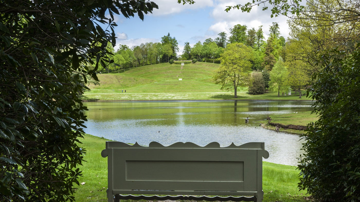 View across the lake towards the turf amphitheatre at Claremont Landscape Garden in Surrey