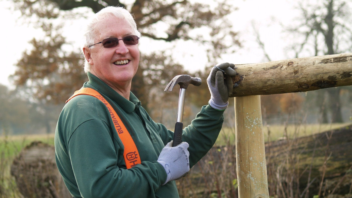 Estate volunteer Colin hammering nails in to a fence post