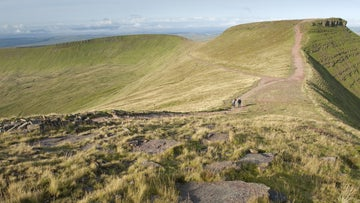 Walkers on the footpath between Corn Du in the distance and Pen y Fan in the Brecon Beacons National Park, South Wales
