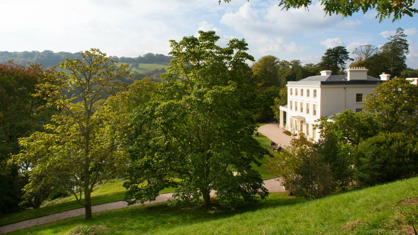 The exterior of Greenway house surrounded by gardens in the autumn