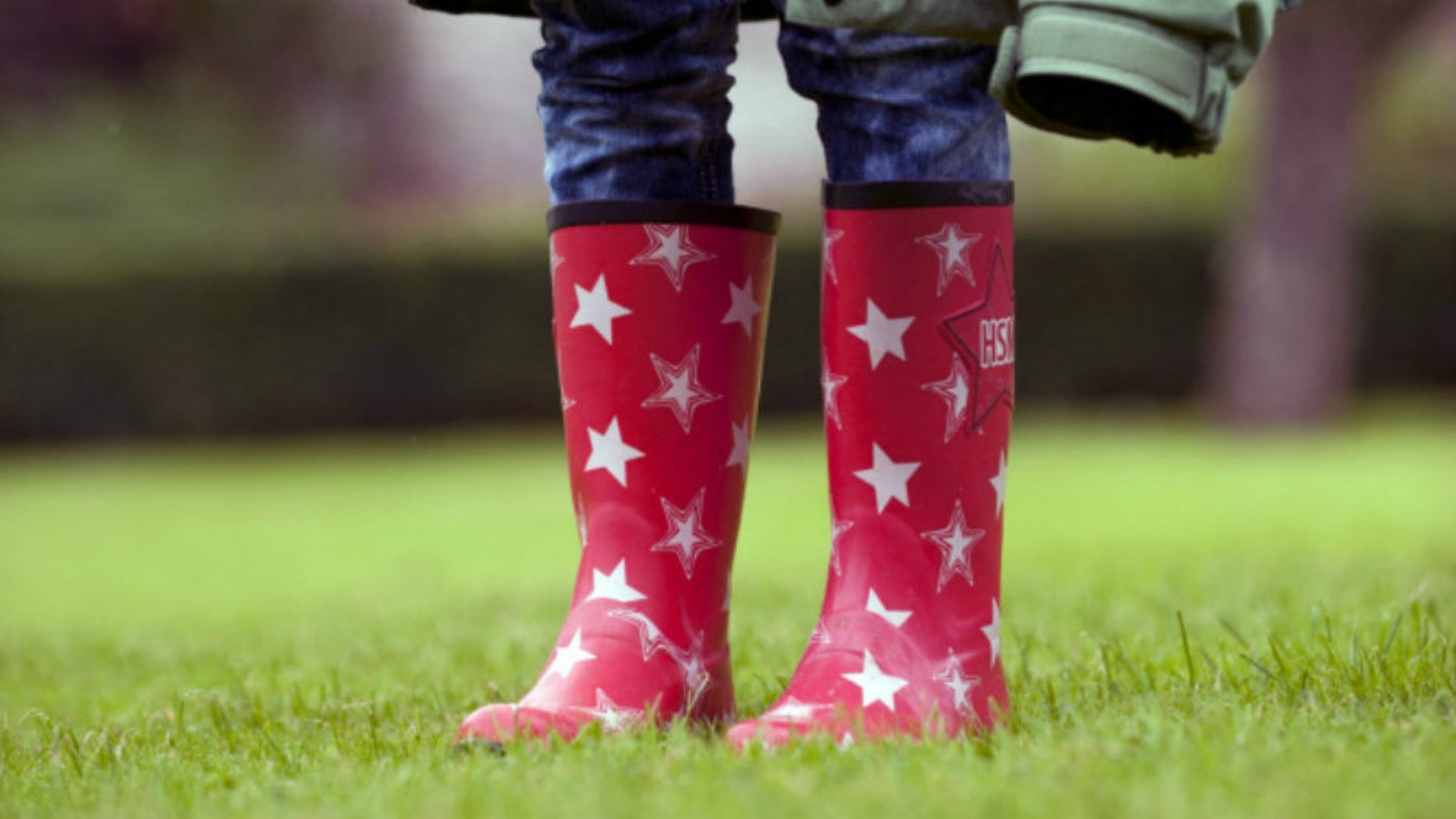 Legs of a child wearing bright red wellies with white stars