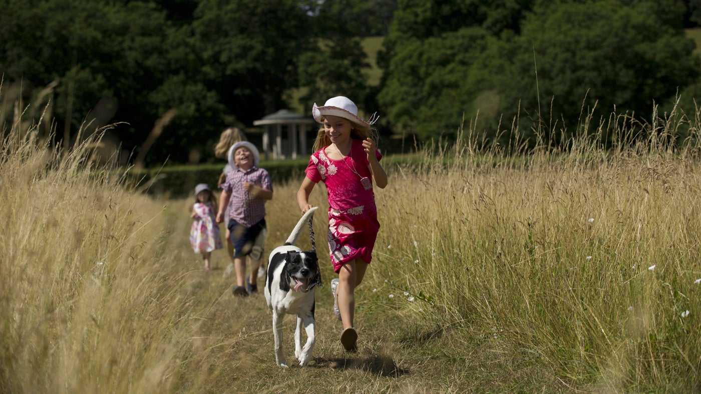Family running through a meadow with their dog with the Magna Carta memorial in the background, at Runnymede in Surrey