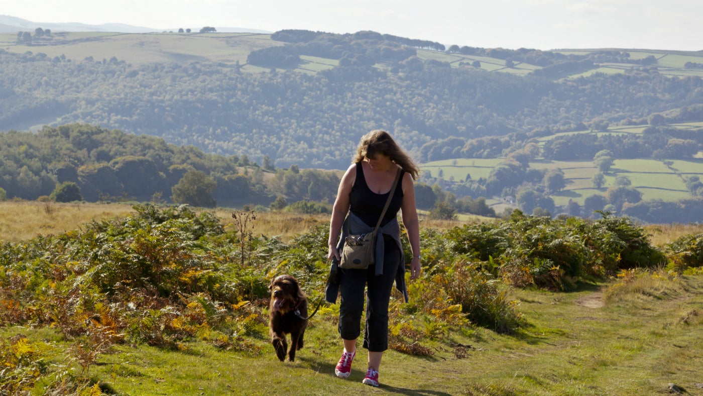 Woman walking with dog on lead in countryside