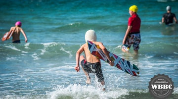 youngsters race into the sea with their bellyboards