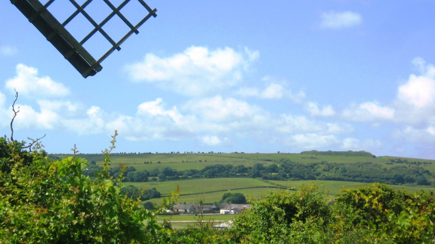 The bulk of Bembridge Down, topped by the nobbly Bembridge Fort, is viewed from beneath the sails of Bembridge Windmill