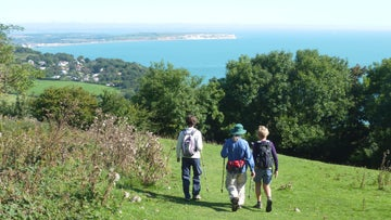 Three walkers on Luccombe Down with fine views over Sandown Bay
